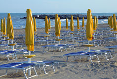 Closed Sun umbrellas on sea beach with sun loungers and deckchai Stock Photos