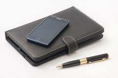 Closed tablet and android mobile phone and gold pen.  stock images