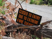 Closed to entery due to extreme fire danger. A sign warns that the road is closed due to extreme fire hazard. A gravel road into a heavy wooded area of the royalty free stock photo