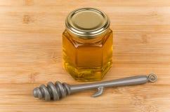 Closed transparent jar of honey and plastic stick Stock Image