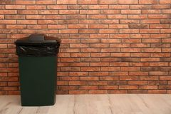 Closed trash bin near brick wall indoors, space for text. Waste recycling stock image