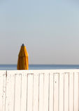 Closed umbrella of a bathing establishment. A closed umbrella in a bathing establishment, behind a white wooden fence, at the beach of mondello, near palermo Stock Photo