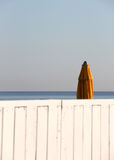Closed umbrella of a bathing establishment. A closed umbrella in a bathing establishment, behind a white wooden fence, blurred, at the beach of mondello, near Royalty Free Stock Photos