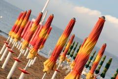 Closed umbrellas on the beach Royalty Free Stock Photos