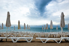 Closed umbrellas and deckchairs on the empty beach Royalty Free Stock Photography
