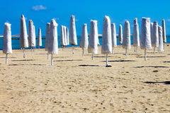 Closed umbrellas in an empty beach Stock Photography