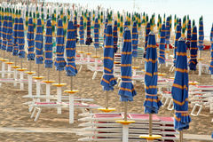 Closed umbrellas in line on the beach Stock Photo