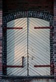 Closed and unlocked door at wall. Closed and unlocked, old white door at red brick wall Stock Image