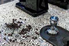 Closed up Arabica coffee beans scattered in glass saucer on croc. Het tablecloth with blurred coffee tamper. Vintage display on flower crochet pattern Stock Photography