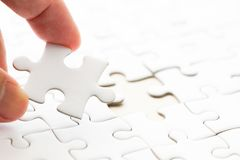 Background of white plain jigsaw with hand that hold missing piece. Closed up background of white plain jigsaw with hand that hold missing piece to match or royalty free stock images