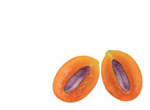 Closed up bright orange color fresh ripe Marian Plum fruit cut in half with purple seed on white background Stock Photography