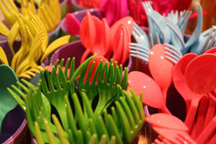 Closed up bunch of multi-color plastic ware cutlery with selective focus stock photo