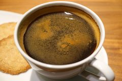 Closed up a cup of black coffee in a white cup served with some cookies. Selective focus Stock Photo