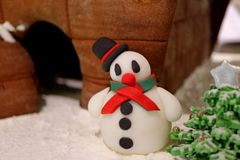 Closed Up a Cute Snowman Marzipan with Ginger Bread House and Candy Christmas Tree royalty free stock photography