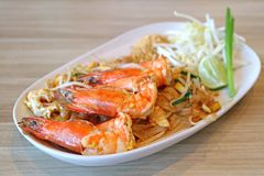 Closed Up Delectable River Prawns Topped on Pad Thai or Thai Style Fried Noodle Served on Wooden Table royalty free stock image