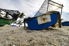 Closed up fisherman boat stranded on the sandy beach and cloudy sky royalty free stock images