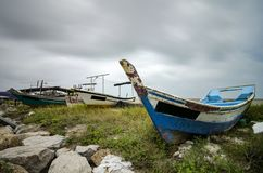 Closed up fisherman boat stranded on the sandy beach and cloudy sky royalty free stock image