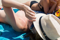 A closed-up girl in a hat on a beach with a friend Stock Photos