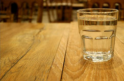 Closed up a glass of water on natural brown wooden table with selective focus Royalty Free Stock Photography