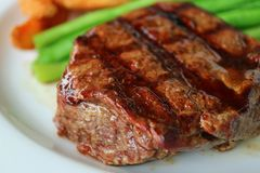 Closed Up Grilled Tenderloin Steak with Blurred Vegetable in Background stock image
