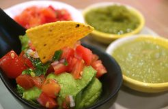 Closed Up Guacamole with Nachos Chip and Blurred Colorful Spicy Mexican Salsa Sauce in Background stock image
