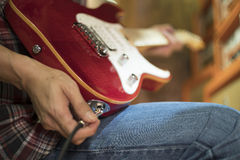 Closed up hand holding jack plug-in to the electric guitar Stock Photos