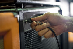 Closed up hand holding jack plug-in to the guitar amplifier Stock Images