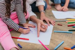 Closed up hands of mom teaching little children to drawing cartoon in art class with color pen. Back to school and Education