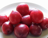 Closed up Heap of Ripe Gulf Ruby Plum Fruits on a White Plate Royalty Free Stock Photos