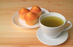 Closed up hot green tea on wooden table, with blurred madeleine cupcake in the background Stock Photography