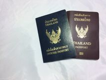 Thai passports. Closed up image of two Thai passports. Blue one is for official government officers, brownone is for regular use stock photos