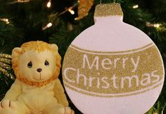 Closed up Little Cute Lion with White and Gold Merry Christmas Ornament on a Sparkling Christmas Tree. Happy Holidays royalty free stock photos