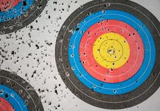Closed up many arrow holes on yellow, blue, and red target. Closed up many arrow holes on yellow, blue, and red archery target royalty free stock image