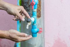 Closed up metal water faucet which is closed by right hand. Water shortage Royalty Free Stock Photo