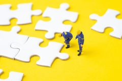 Closed up of miniature people worker or staffs looking at the white jigsaw puzzle pieces on yellow background with copy space, stock images