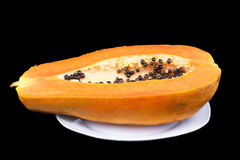 Closed-up papaya on plate isolated on black Royalty Free Stock Image