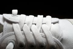 Closed-up photo of white sneaker on dark background stock images