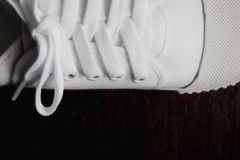 Closed-up photo of white sneaker on dark background