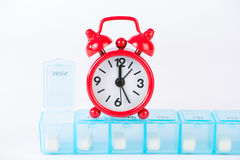 Closed up daily pill box and red alarm clock Stock Images