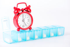 Closed up daily pill box and red alarm clock Royalty Free Stock Photography