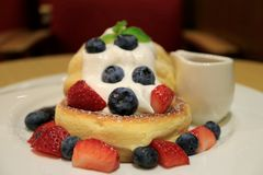 Closed Up a Plate of Fresh Mix Berries Souffle Pancake with Mascarpone Cream and Syrup royalty free stock photo