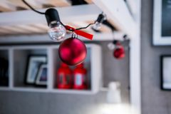 Closed up red Christmas balls hanging on black string light bulb. Set for decoration against blurred background Stock Images