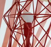 Closed up red decorative wire lamp with white bulb in the middle stock image