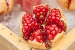 Closed up red pomegranate fruit. On ice basket Stock Image