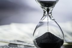 Closed up of sand falling in sandglass or hourglass on US Dollar. Bills as time running, long term investment or financial deadline concept Royalty Free Stock Photography