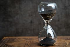 Closed up of sandglass or hourglass on vintage book with dark bl. Ack loft cement background using as time symbol or business deadline counting down concept Royalty Free Stock Images