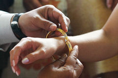 Closed-up Thai traditional man putting wedding bracelet on engagement process Royalty Free Stock Images