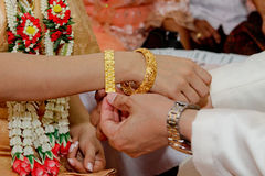 Closed-up Thai traditional man putting wedding bracelet on engagement process Stock Photography