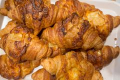 Closed up traditional butter croissant with cheese topping on white tray stock image