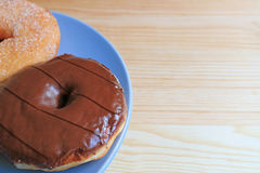 Closed up two types of doughnuts served on blue plate on the wooden table, with free space for design Stock Image